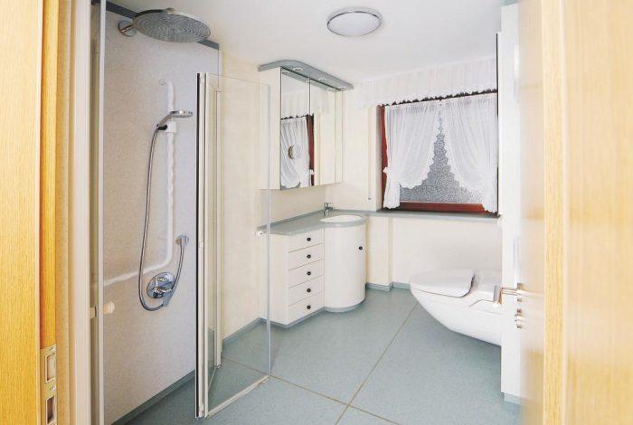 Betrachtung der Badlösung durch die Eingangstüre aus dem Wohnzimmer in modularer Bauweise und Creanit® Boden