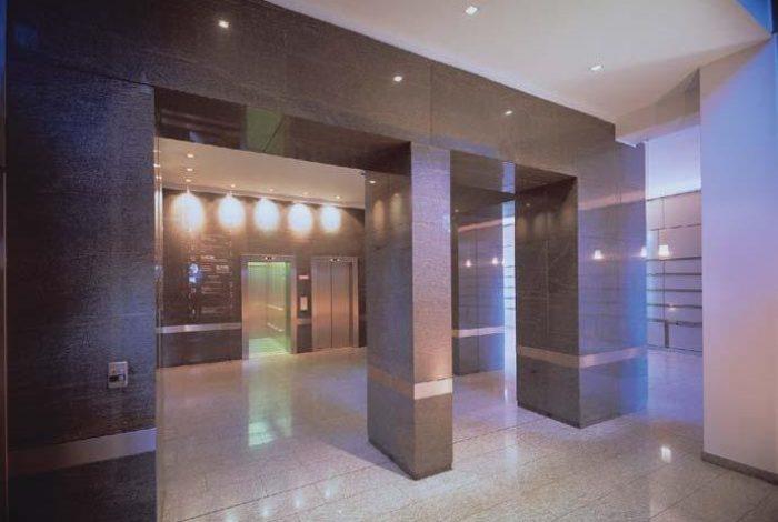 Eingangshalle in das Bürogebäude mit Gramablend verkleidet. In der gleichen Ausführung ist auch der gesamte Aufzugturm realisiert