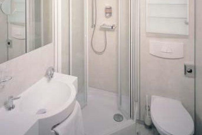 Gästezimmer mit DU geöffneter Duschglastüre und  minimaler Ausstattung