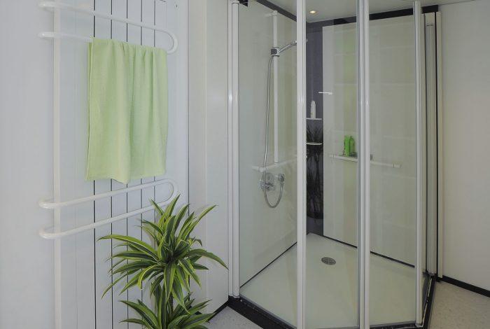 Duschkabine geschlossen, links Heizkörper mit Badetuchbügel
