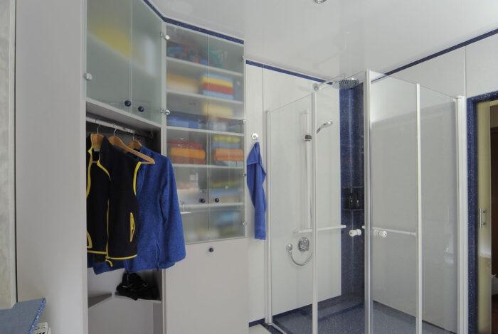 Kleider und Wäscheschrank mit geschlossenen Duschtüren, ganz rechts geöffnete Schiebetüre