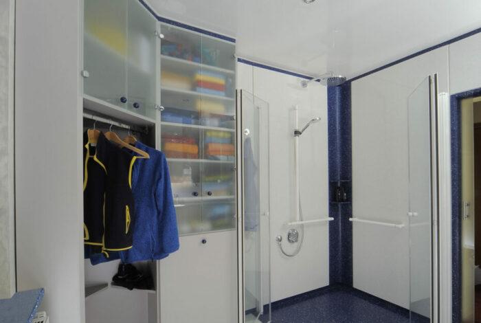 Kleider und Wäscheschrank mit nach außen geöffneten Duschtüren, ganz rechts geöffnete Schiebetüre