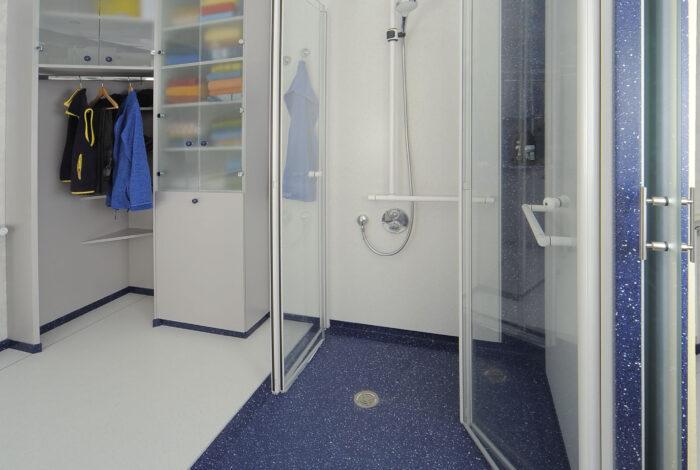 Kleider und Wäscheschrank und nach innen geöffneten Duschtüren, ganz rechts geöffnete Schiebetüre